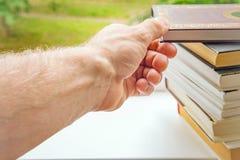 Handtagande bokar från högen av bokcloseupen royaltyfri fotografi