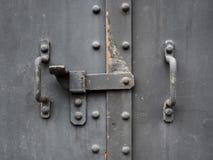 Handtaget för metalldörrporten med låset texturerade yttersida Arkivbild