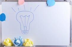 Handtekening lightbulb en verfrommeld document op de witte bureauraad als symbool van creatief en het denken over nieuwe ideeën stock foto's