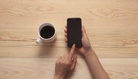 Handtelefon und -kaffee auf hölzernem Hintergrund stockbild