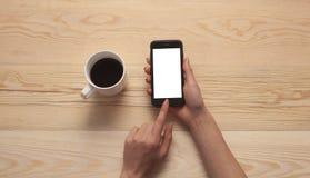 Handtelefon und -kaffee auf hölzernem Hintergrund stockbilder