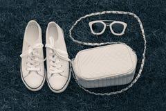 Handväska, gymnastikskor och solglasögon med gräs som en bakgrund Fotografering för Bildbyråer