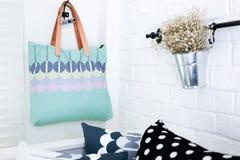 Handväskan hängde på den vita tegelstenväggen med färgrika kuddar royaltyfri fotografi