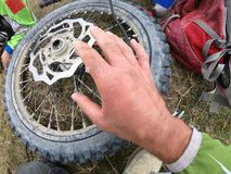 Handverwonding op motorfiets en Wielreparatie in de bergen royalty-vrije stock afbeeldingen