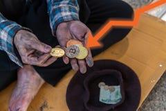 Handvol bitcoinmuntstukken in de handen van een bedelaar stock foto