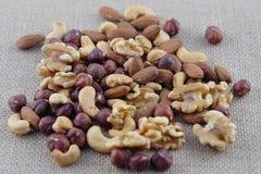 Handvol cashewnoten, amandelen, okkernoten en hazelnoten op een jutestof Selectieve nadruk stock foto