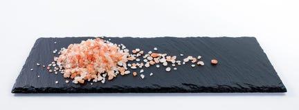 Handvol van roze Hymalayan-zout op donkere schalieplaat Stock Afbeeldingen
