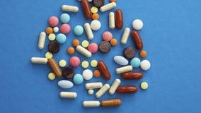 Handvoll farbige Pillen zerstreut auf blauen Hintergrund stock video footage