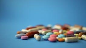 Handvoll farbige Pillen zerstreut auf blauen Hintergrund stock video