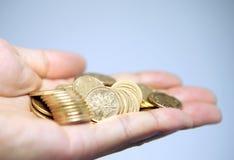 Handvoll Münzen in der Palmenhand Lizenzfreie Stockfotos