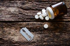 Handvoll von Pillen und von Blatt für Selbstmord auf einem hölzernen Lizenzfreie Stockfotos