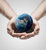 Handvollboden mit der Erde in den männlichen Händen Stockbilder