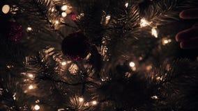 Handvrouw wat betreft Kerstmisbal op boom met bokehlichten in de langzame motie van de Kerstmistijd stock video