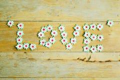 Handwerk der Papierblume setzte einen Buchstaben des Liebeswortes auf Holzfußboden Lizenzfreies Stockfoto