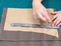 Handwerker befestigt das Papiermuster am Gewebe lizenzfreie stockfotos
