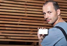 Handwerker, der eine Visitenkarte anhält Lizenzfreie Stockbilder