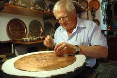 Handwerker, der einen kupfernen Teller in Mostar bastelt Stockfotografie