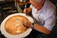 Handwerker, der einen kupfernen Teller in Mostar bastelt Stockbild