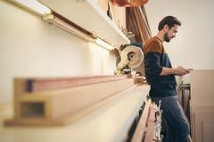 Handwerker, der Handy in seiner Werkstatt verwendet stockfotos