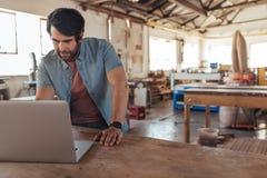 Handwerker, der online mit einem Laptop in seinem Holzbearbeitungsshop arbeitet stockbild