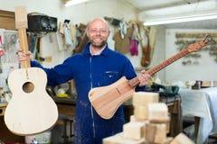 Handwerker, der unfertige Gitarre hält lizenzfreie stockfotos
