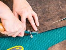 Handwerker markiert Muster auf dem geschnitzten Leder stockbilder