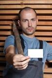Handwerker mit einem Hammer, der eine Visitenkarte anhält Lizenzfreie Stockfotos