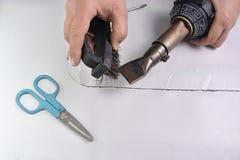 Handwerker säubert Düse mit einer Stahlbürste Stockbilder