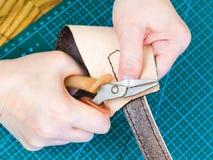 Handwerker stellt den Gurt für Lederhandtasche her stockbilder