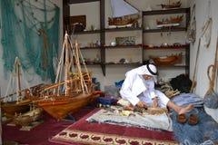 Handwerker von Katar in der traditionellen Kleidung, die handgemachtes h?lzernes Modell von Schiffen schafft stockfotos