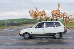 Handwerker zeigt Transportmethode von Korbwaren auf einem Dach des kleinen Autos Stockbild