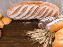 Handwerkerbrotlaibe und Weizenstiele Stockbild