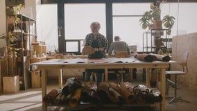 Handwerkerin, die ein großes Stück Leder auf einer großen Tabelle in einer modernen Herstellungswerkstatt für kleines lokales Unt stock footage