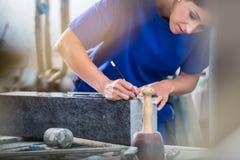 Handwerkerin, die Schablone für das Gravieren auf Grundstein anwendet lizenzfreie stockfotografie