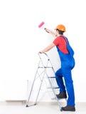 Handwerkermaler steht auf der Treppe mit Rolle Stockfotos
