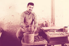 Handwerkermann, der herein keramisches Stück auf spinnender Töpferscheibe schafft lizenzfreie stockbilder