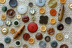 Handwerks-nähende Knöpfe auf Gewebes-Hintergrund Stockfotos