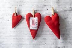 Handwerks-Tag Rastre Bild Handgemachte rote Textilherzen wiegen auf einem Seil, befestigt mit einer Wäscheklammer lizenzfreies stockbild