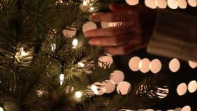 Handwijfje wat betreft Kerstboom met bokehlichten in Kerstmistijd stock videobeelden