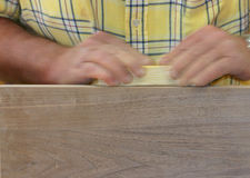 Handwork 1. Two hands in motion sanding a piece of wood stock photo