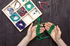 Handwork hemma, flickan gör smyckenhänder på tabellen fotografering för bildbyråer