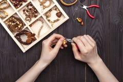 Handwork hemma, flickan gör smyckenhänder på tabellen royaltyfria foton