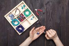 Handwork hemma, flickan gör smyckenhänder på tabellen royaltyfri fotografi