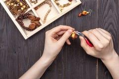 Handwork hemma, flickan gör smyckenhänder på tabellen royaltyfria bilder