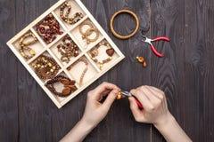 Handwork hemma, flickan gör smyckenhänder på tabellen royaltyfri bild