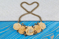 Handwork necklace of on a golden chain, laid out in the shape of a heart is lies on a blue wooden background Royalty Free Stock Image