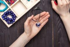 Handwork thuis, het meisje maakt juwelenhanden op de lijst royalty-vrije stock afbeelding