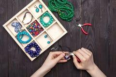 Handwork thuis, het meisje maakt juwelenhanden op de lijst stock foto