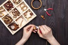 Handwork thuis, het meisje maakt juwelenhanden op de lijst stock afbeelding