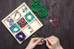 Handwork thuis, het meisje maakt juwelenhanden op de lijst royalty-vrije stock afbeeldingen